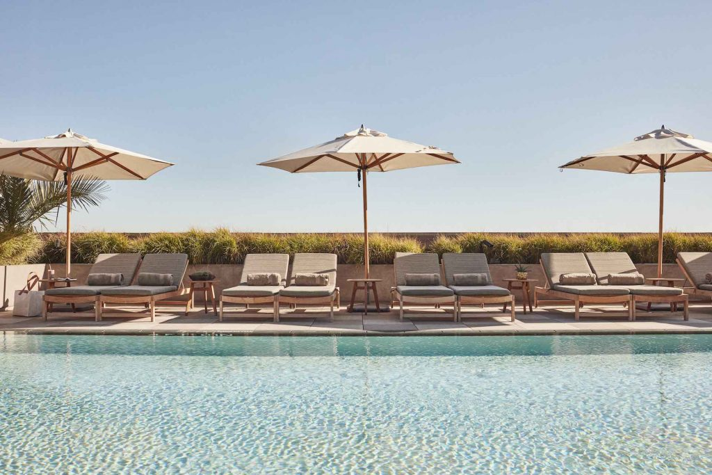 Guests can change up their space (or take a break) by the hotel pool.