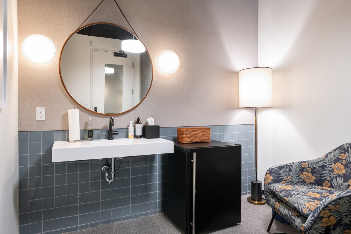This wellness room contains a comfortable chair, mini fridge, and sink, and can be locked for privacy.